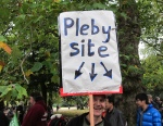 Picture of a protester holding a sign referencing Andrew Mitchell, involved in the 'plebgate' police misconduct case.